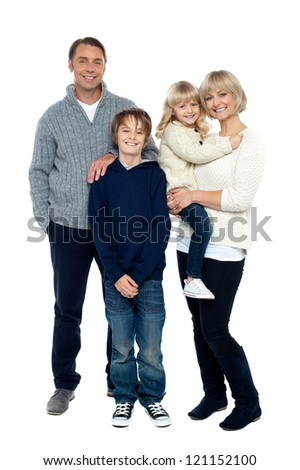 Full length portrait of a happy family posing in trendy winter wear outfits. - stock photo