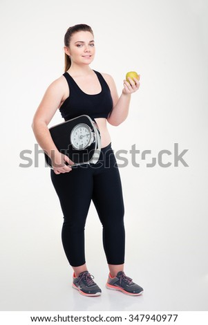 Full length portrait of a happy fat woman holding weighing machine and apple isolated on a white background