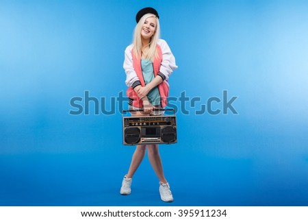 Full length portrait of a happy female teenager holding retro boom box on blue background - stock photo