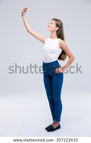 Full length portrait of a happy female teenager making selfie photo on smartphone isolated on a white background - stock photo
