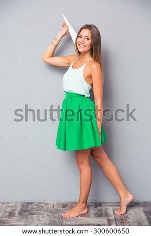 Full length portrait of a happy girl holding paper plane and looking at camera - stock photo
