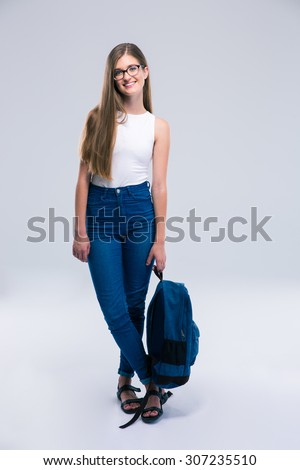 Full length portrait of a happy girl in glasses holding backpack isolated on a white background - stock photo