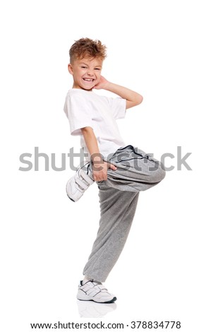 Full length portrait of a happy little boy dancing isolated on white background