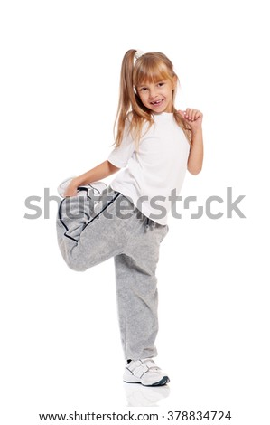 Full length portrait of a happy little girl dancing isolated on white background