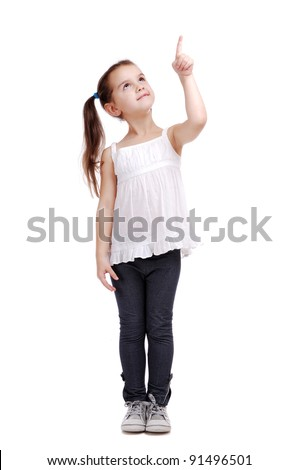Full length portrait of a happy little girl standing pointing with finger on white background