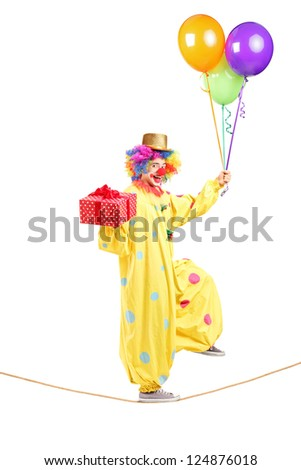 Full length portrait of a happy male clown walking on a rope with bunch of balloons and present isolated on white background - stock photo