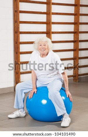 Full length portrait of a happy senior woman sitting on fitness ball at hospital gym - stock photo