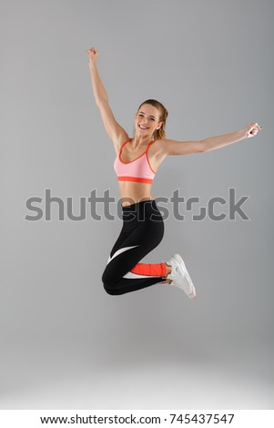 Full length portrait of a happy smiling sportsgirl celebrating success and jumping with hands outstretched isolated over gray background