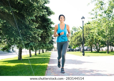 Full length portrait of a happy sports woman running outdoors - stock photo