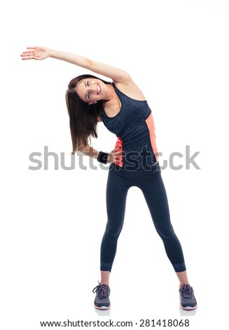 Full length portrait of a happy sporty woman doing stretching exercise isolated on a white background. Looking at camera - stock photo