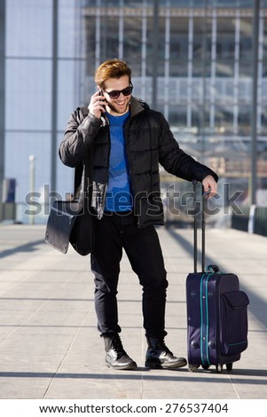 Full length portrait of a happy traveling man talking on mobile phone at airport - stock photo