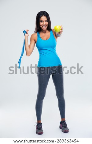 Full length portrait of a happy woman holding apple and measuring tape over gray background. Looking at camera - stock photo