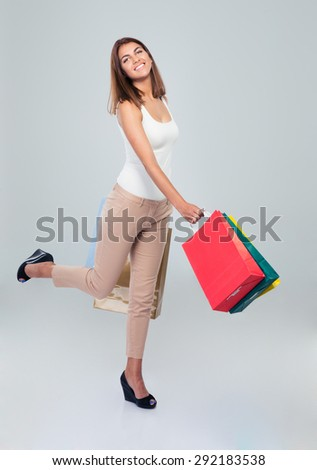 Full length portrait of a happy woman holding shopping bags over gray background and looking at camera - stock photo