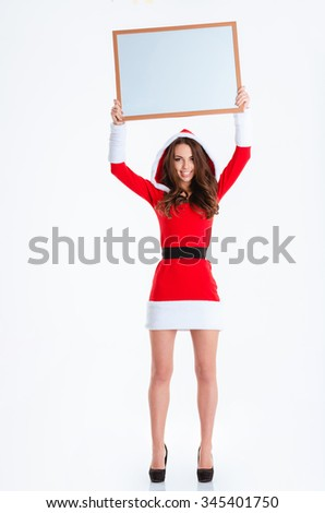 Full length portrait of a happy woman in santa claus cloth holding blank board over head isolated on a white background