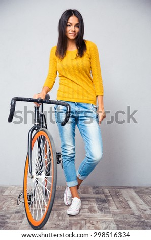 Full length portrait of a happy woman stnading with bicycle on gray background and looking at camera - stock photo