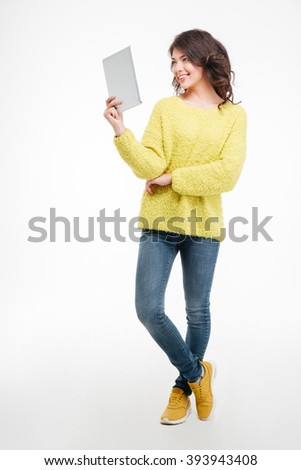Full length portrait of a happy woman using tablet computer isolated on a white background - stock photo