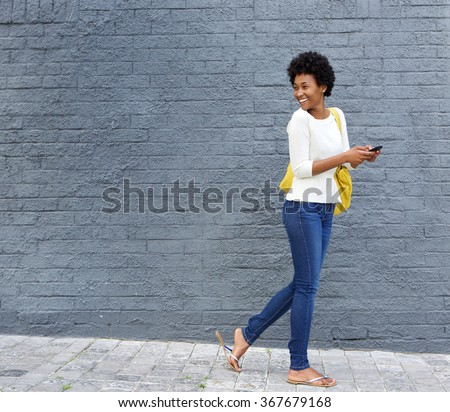 Full length portrait of a happy young african woman with a mobile phone walking on street and looking over her shoulder - stock photo