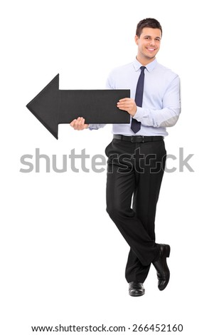 Full length portrait of a happy young businessman holding a big black arrow pointing right and leaning against a wall isolated on white background