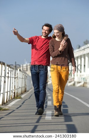 Full length portrait of a happy young couple walking outdoors on their date - stock photo