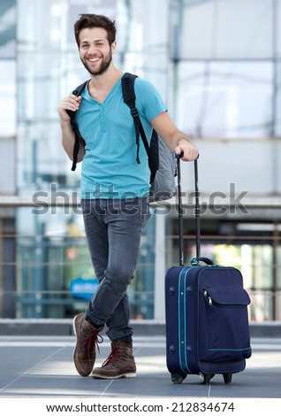 Full length portrait of a happy young man waiting at airport with suitcase and bag - stock photo