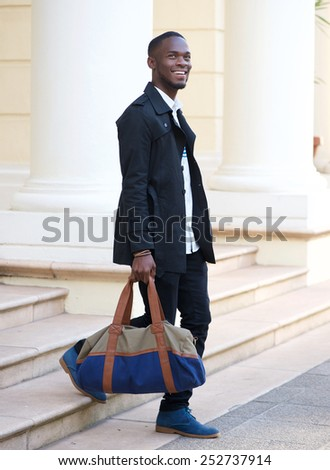 Full length portrait of a happy young man walking down steps of hotel with bag - stock photo