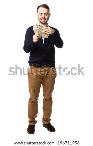 Full length portrait of a happy young man with a beard smiling and showing off a handful of money with fanned dollar bills in his hand - stock photo