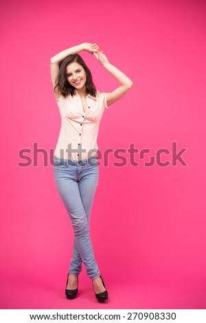 Full length portrait of a happy young woman posing over pink background. Wearing in jeans and shirt. Looking at camera - stock photo
