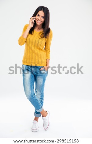 Full length portrait of a happy young woman talking on the phone isolated on a white background - stock photo
