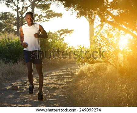 Full length portrait of a healthy african american man jogging in nature - stock photo