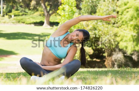 Full length portrait of a healthy and beautiful young woman doing stretching exercise in the park