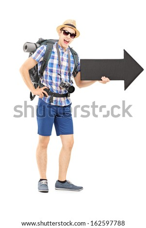 Full length portrait of a hiker with backpack holding a big black arrow isolated on white background