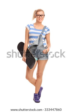 Full length portrait of a hipster girl holding a skateboard and looking at the camera isolated on white background - stock photo