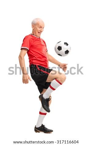 Full length portrait of a joyful senior juggling a football and smiling isolated on white background - stock photo
