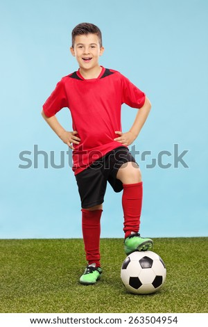 Full length portrait of a junior in a soccer uniform standing over a soccer ball on a grass field with a blue background  - stock photo