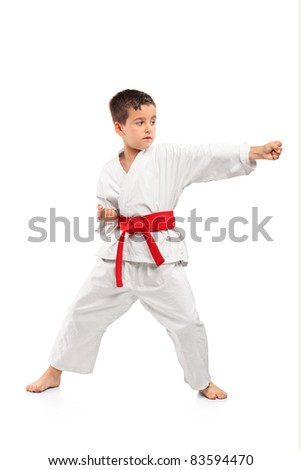 Full length portrait of a karate child exercise isolated on white background