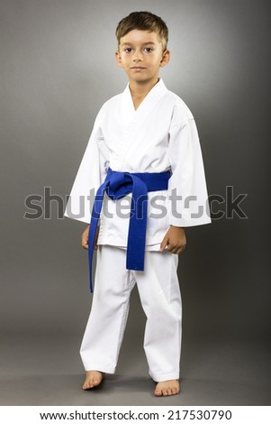 Full length portrait of a karate kid  in kimono isolated on gray background - stock photo