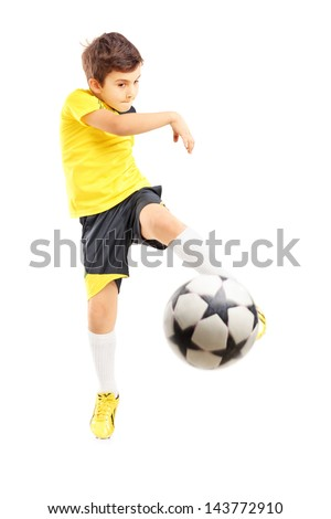 Full length portrait of a kid in sportswear shooting a soccer ball isolated on white background - stock photo