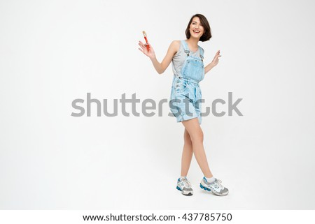 Full length portrait of a laughing pretty girl, in gray shirt and denim overall, holding painting brush, isolated on white background - stock photo