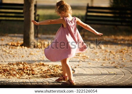 Full length portrait of a little girl dancing in the park a warm autumn evening. In move. Back view - stock photo