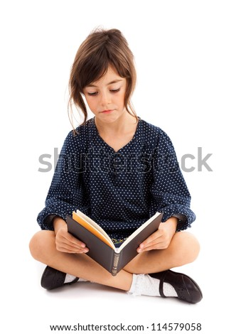 Full length portrait of a little girl reading while sitting with crossed legs - stock photo