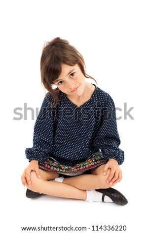 Full length portrait of a little girl sitting with crossed legs isolated on white
