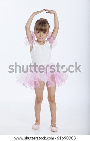 Full length portrait of a little pretty ballerina performing a new ballet position, studio image