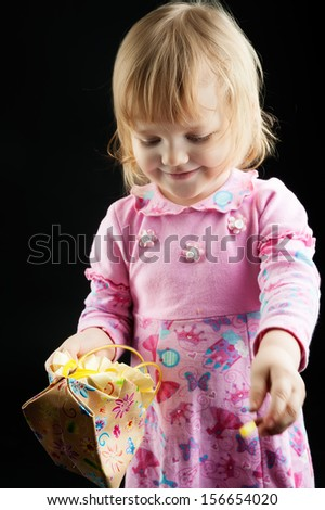 Full length portrait of a little 2 years old girl standing with handbag over black background - stock photo