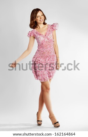 Full-length portrait of a lovely brunette woman in romantic dress - stock photo