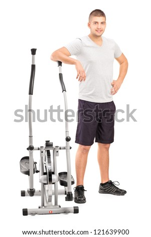 Full length portrait of a male athlete standing next to a cross trainer machine isolated on white background