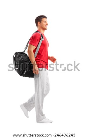 Full length portrait of a male athlete walking with a sports bag isolated on white background