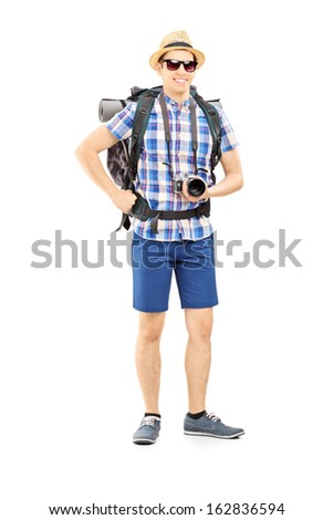 Full length portrait of a male hiker with backpack and camera posing isolated on white background - stock photo