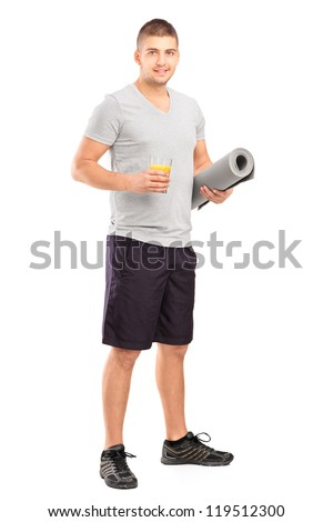 Full length portrait of a male holding a glass of orange juice and a mat after an excerise isolated on white