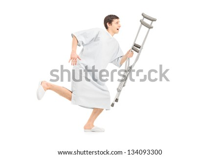 Full length portrait of a male patient running and holding a crutch, isolated on white background - stock photo