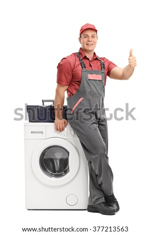 Full length portrait of a male repairman leaning on a washing machine and giving a thumb up isolated on white background